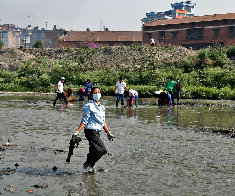 FILE - A girl is seen cleaning Bagmati River under Bagmati clean-up campaign, in Thapathali, Kathmandu, on Saturday, April 29, 2017. Photo: RSS
