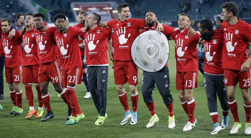 Bayern's Arturo Vidal carries a mock trophy as he and his teammates celebrate winning the German soccer champion title after the Bundesliga soccer match against VfL Wolfsburg in Wolfsburg, Germany, on Saturday, April 29, 2017. Photo: AP