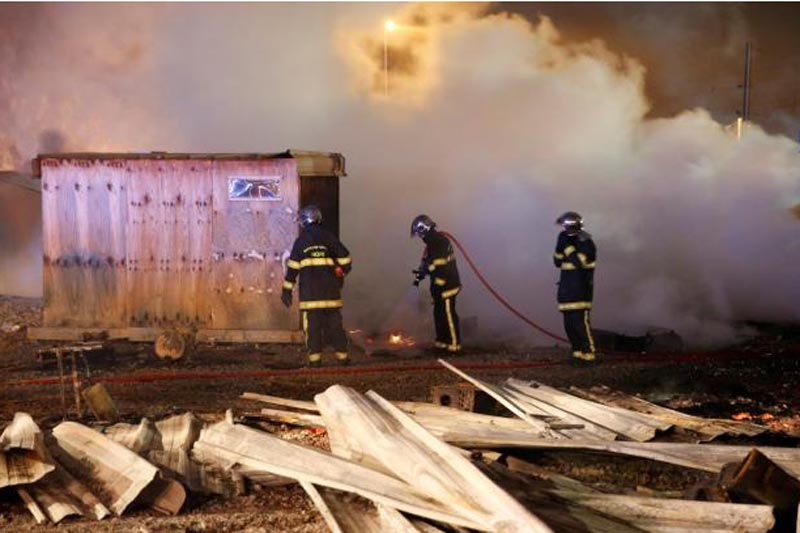 Firefighters extinguish shelters during a fire which destroyed many wood houses at a camp for migrants in Grande-Synthe, near Dunkirk, France, April 11, 2017. Photo: Reuters