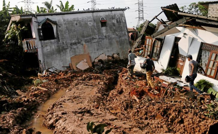 People walk past damaged houses during a rescue mission after a garbage dump collapsed and buried dozens of houses in Colombo, Sri Lanka April 15, 2017. REUTERS/Dinuka Liyanawatte