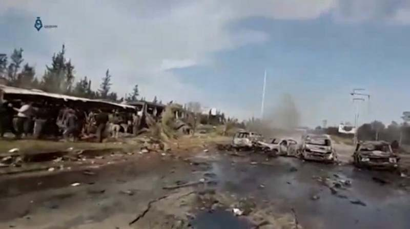 A still image taken from a video uploaded on social media on April 15, 2017, shows burnt out buses on road, scattered debris lying nearby and injured people being tended to away from buses said to be in Aleppo, Syria. Photo: Social Media Website via Reuters TV