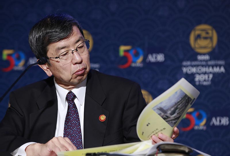 The Asian Development Bank (ADB) President Takehiko Nakao looks at materials during the opening press conference of an ADB annual meeting in Yokohama, near Tokyo, on Thursday, May 4, 2017. Photo: AP