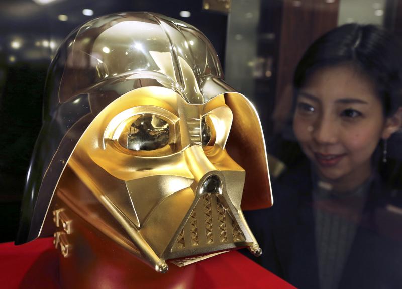 Tokyo gold jeweler Ginza Tanaka employee Momoko Marutani looks at the gold mask of Darth Vader at the jewelry shop in Tokyo, on Monday, May 1, 2017. Photo: AP