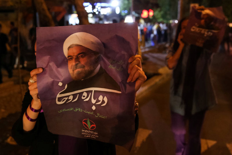 A supporter of Iranian president Hassan Rouhani holds his poster as she celebrates his victory in the presidential election, in Tehran, Iran, on May 20, 2017. Photo: TIMA via Reuters