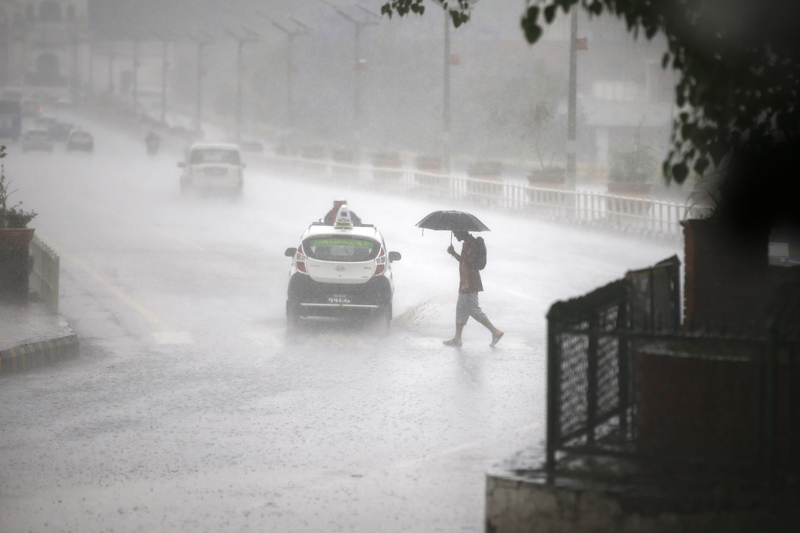 A man holds an umbrella to shield the heavy rainfall as he crosses the road in Kathmandu, on Thursday, May 11, 2017. Photo: Skanda Gautam