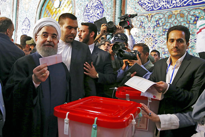 In this photo released by official website of the office of the Iranian Presidency, President Hassan Rouhani holds his ballot while voting for the presidential and municipal councils election at a polling station in Tehran, Iran, on Friday, May 19, 2017. Photo: AP