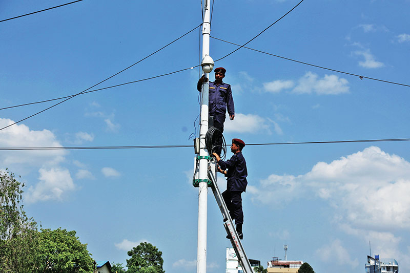 Police personnel installing CCTV on a utility pole in Jamal, on Saturday, May 13, 2017. Photos: THT/ RSS