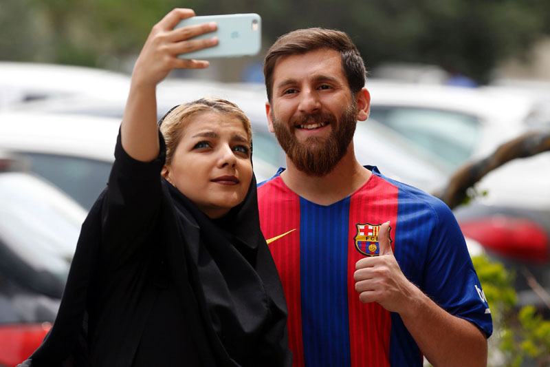 Reza Parastesh, a doppelganger of Barcelona and Argentina's footballer Lionel Messi, poses for a picture with fans in a street in Tehran on May 8, 2017. Photo: AFP