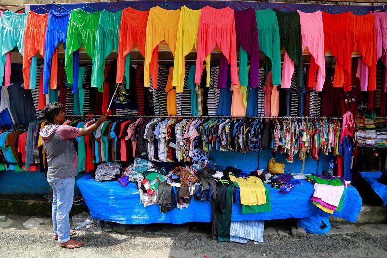 FILE PHOTO: A vendor arranges clothes at his roadside shop in Kochi, India, May 18, 2017. Photo: Reuters