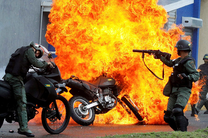 Riot security forces clash with demonstrators as a motorcycle is set on fire during a protest against Venezuelan President Nicolas Maduro's government in San Cristobal, Venezuela on May 29, 2017. Photo: Reuters