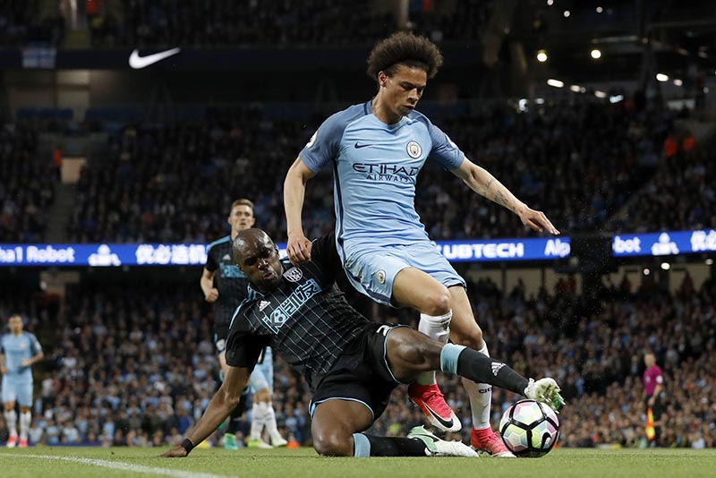 West Bromwich Albion's Allan Nyom (left) and Manchester City's Leroy Sane battle for the ball  during the English Premier League soccer match against Manchester City at the Etihad Stadium, Manchester, England, Tuesday May 16, 2017. Photo: Martin Rickett/PA via AP