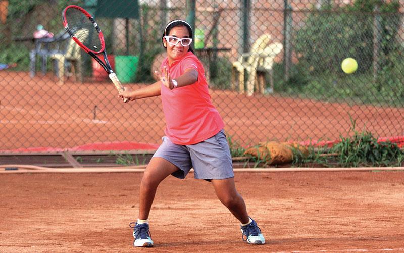 Abhilasha Bista returns to Prakirti Shrestha during their U-18 girlsu0092 singles match of the Nepal Junior Open Lawn Tennis Championship at the Satdobato Tennis Complex in Lalitpur on Wednesday, June 21, 2017. Photo: THT