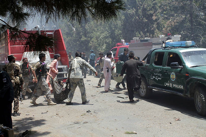 Afghans carry an injured man after a suicide car bombing in Helmand province southern of Kabul, Afghanistan, Thursday, June 22, 2017. Photo: AP