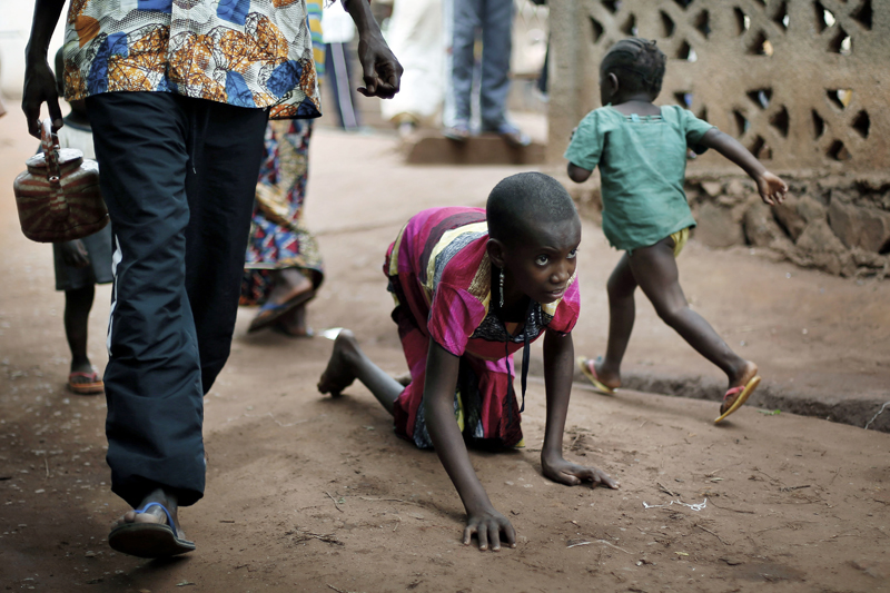 FILE- In this April 14, 2014 photo, Hamamatou Harouna, 10, crawls to the restroom on the grounds of the Catholic Church where she and hundreds of others found refuge in Carnot, Central African Republic. Photo: AP
