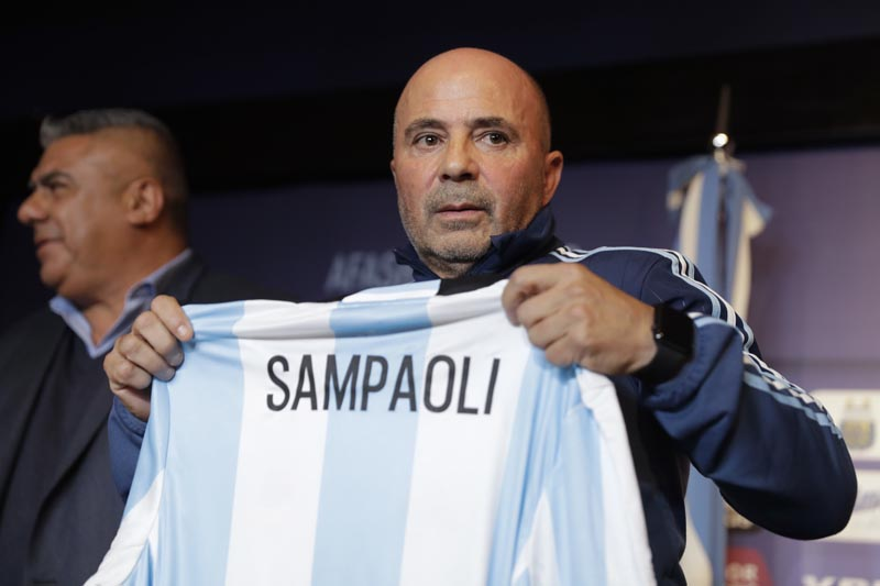 Argentina's new soccer coach Jorge Sampaoli holds up a jersey featuring his name at the end of a press conference in Buenos Aires, Argentina, on Thursday, June 1, 2017. Photo: AP