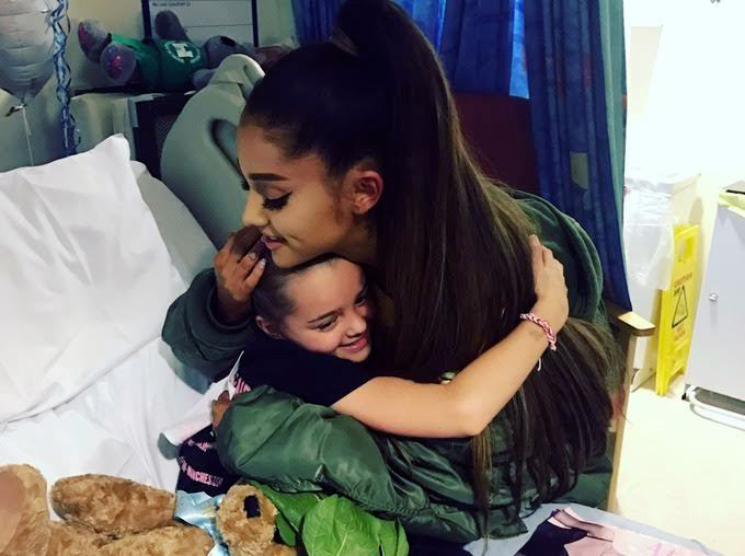 In this photo taken on Friday, June 2, 2017 provided by the Manchester Evening News, victim of the Manchester concert blast Lily Harrison hugs singer Ariana Grande during her visit to the Royal Manchester Children's Hospital, in Manchester, England. Photo: AP