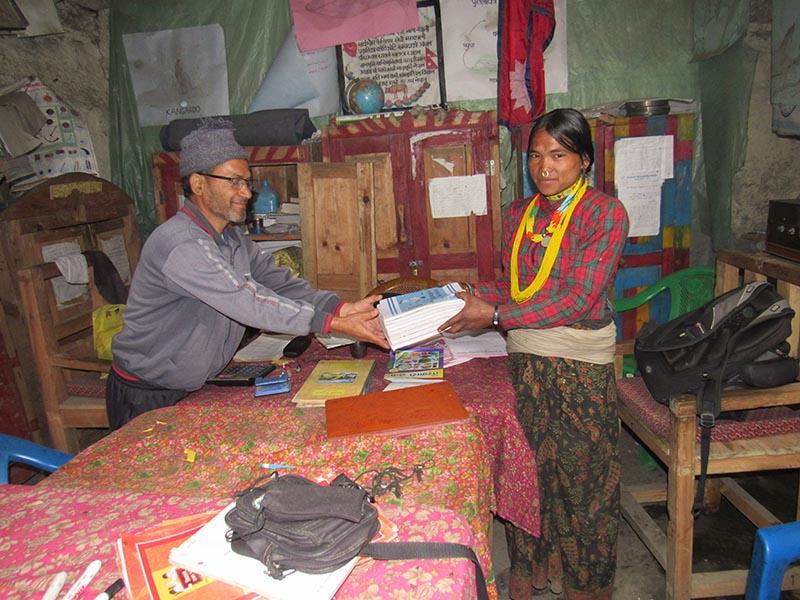 Nim Kala Rokaya, 38, receiving Grade VIII textbooks from a school teacher, in Bajura, on Friday, June 16, 2017. Photo: THT