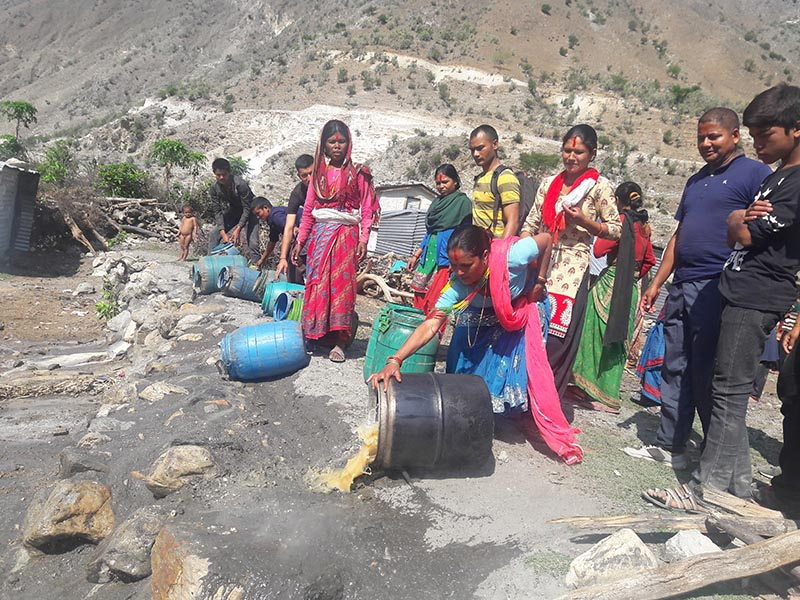 Locals destroying hooch seized by security personnel at Badhu Bazaar of Himali Rural Municipality, in Bajura, on Thursday, June 15, 2017. Photo: THT