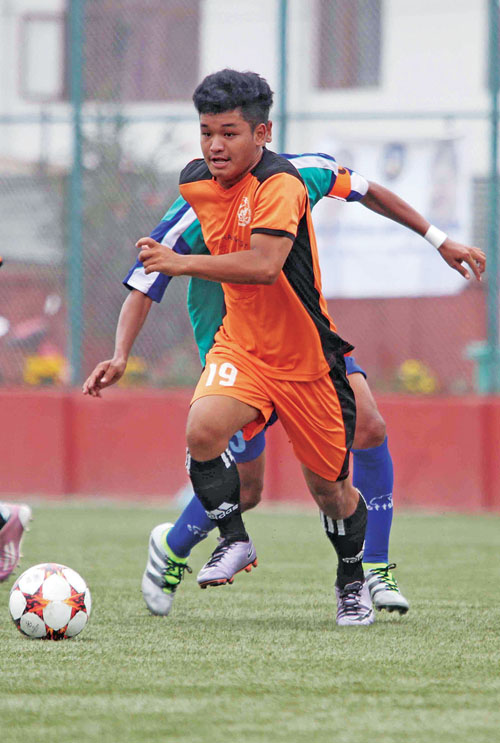 Bel Prasad Gurung of Himalayan Sherpa Club dribbles the ball past Ashok Thapa Magar of New Road Team during their Lalit Memorial U-18 Football Tournament match in Lalitpur on Tuesday, June 06, 2017. Photo: THT