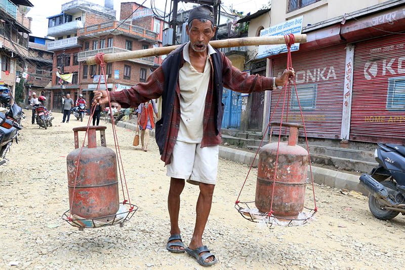 An elderly carries gas cyliners in Bhaktapur, Thursday, June 8, 2017. Photo: RSS