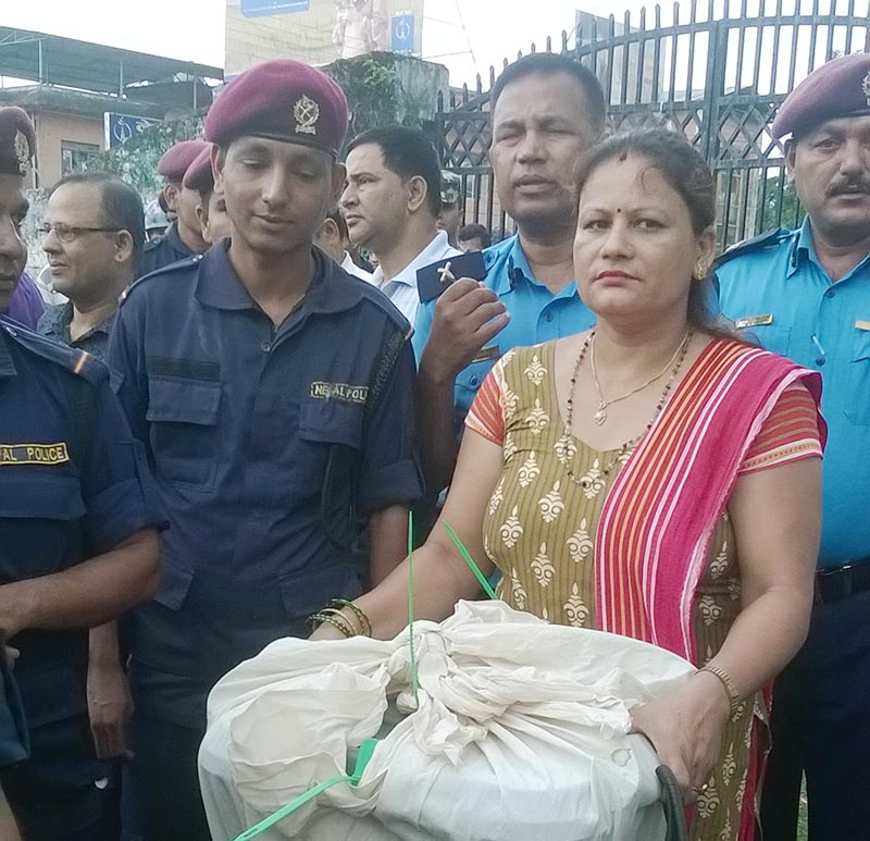 Security personnel guarding an office assistant Laxmi Lamichhane at the Chief Returning Officeru2019s Office Chitwan, while she carries the sealed ballot box from the covered hall in Bharatpur Metropolitan City-10, in Chitwan district, on Tuesday, June 27, 2017. Photo: Tilak Rimal/THT