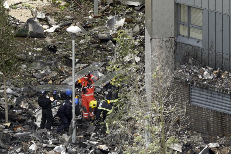 Emergency workers search debris that fell at the base of the fire-gutted Grenfell Tower in London, Friday, June 16, 2017, after a fire engulfed the 24-story building Wednesday morning. London firefighters combed through the burned-out public housing tower Thursday in a grim search for missing people as police and the prime minister launched investigations into the deadly inferno, with pressure building on officials to explain the disaster and assure that similar buildings around the country are safe. Photo: AP