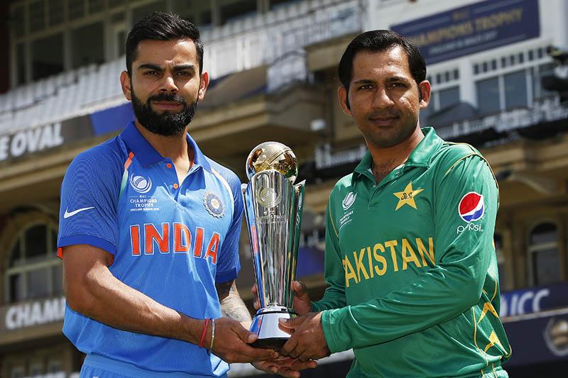 Pakistan's Sarfraz Ahmed and India's Virat Kohli pose with the trophy. Photo: Reuters
