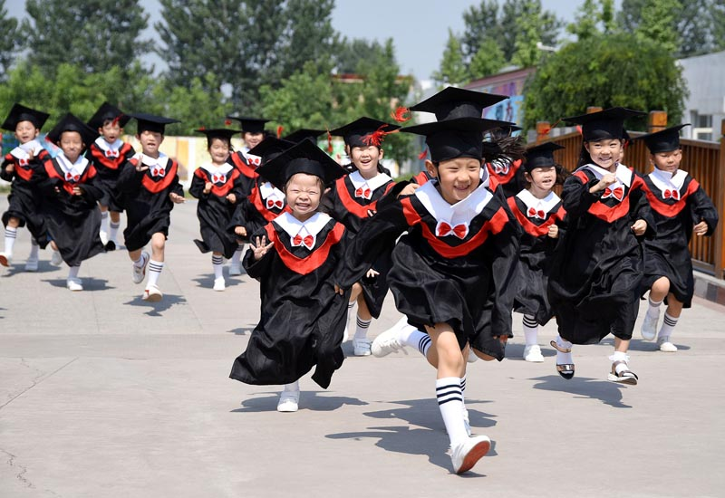 Children in gowns and mortarboards run with smiles during their kindergarten graduation ceremony in a kindergarten in Handan, Hebei province, China, on June 20, 2017. Photo: China Daily via Reuters