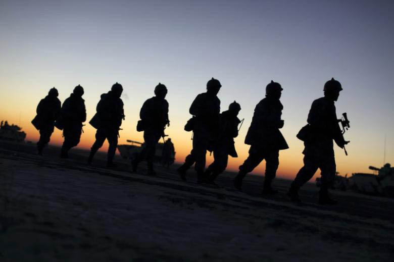 Soldiers of the People's Liberation Army (PLA) Marine Corps march during a military drill as the sun rises at a military base in Taonan, Jilin province January 28, 2015. Photo: Reuters