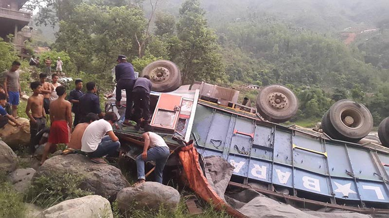 People examine the wrecked truck (Na 6 Kha 3123) that plunged down 50 metres over Hugdikhola Bridge onto the river bank along the Prithvi Highway in Dhading district, on Friday, June 22, 2017. Photo: Keshav Adhikari/THT