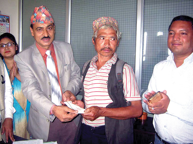 Chief District Officer Prahlad Pokharel (left) handing over the first instalment of housing grant to an earthquake victim, in Khotang, on Saturday, May 03, 2017. Photo: THT