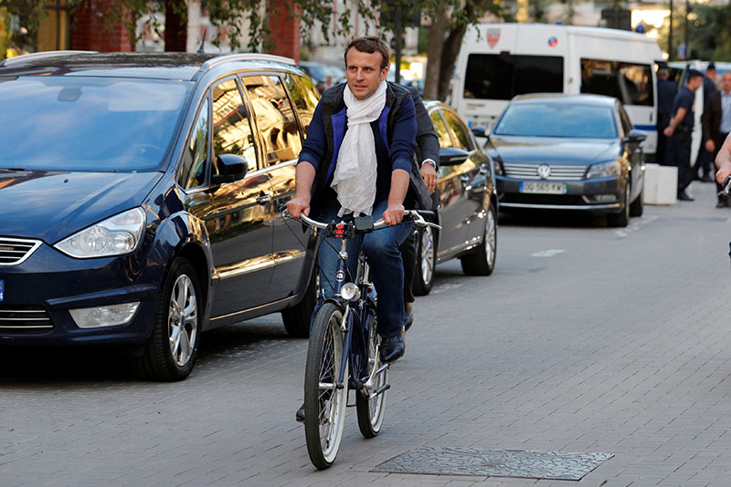 French President Emmanuel Macron arrives at his home on bicycle in Le Touquet, on the eve of the first round of the parliamentary election, France on June 10, 2017. Photo: Reuters