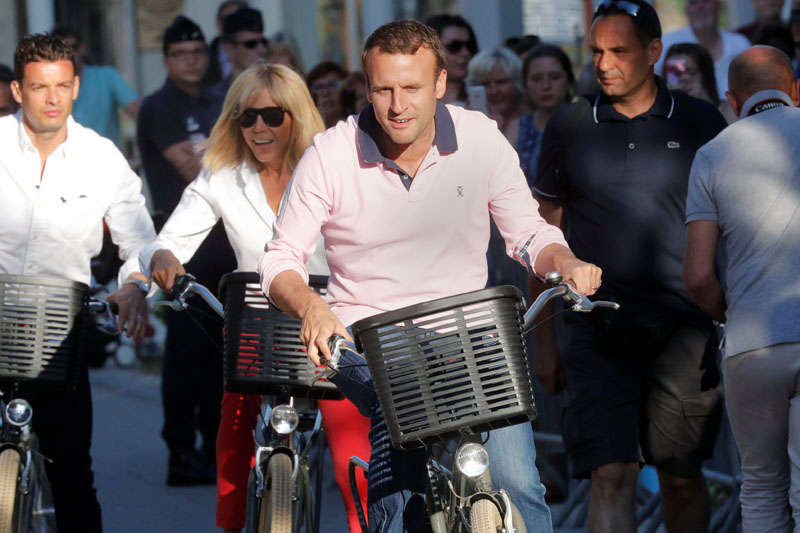 French President Emmanuel Macron and his wife Brigitte Trogneux ride their bicycles as they leave their home in Le Touquet, France on June 17, 2017. Photo: Reuters