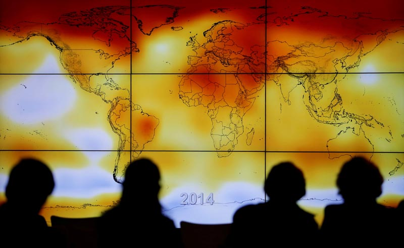 Participants are seen in silhouette as they look at a screen showing a world map with climate anomalies during the World Climate Change Conference 2015 (COP21) at Le Bourget, near Paris, France, on December 8, 2015. Photo: Reuters/ File