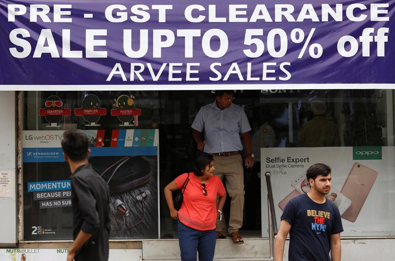 A banner promotes Goods and Services Tax (GST) clearance sale as customers walk out of an electronic shop at a market in New Delhi, India, on June 22, 2017. Photo: Reuters