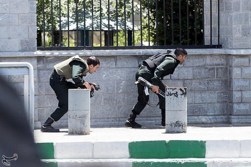 Members of Iranian forces take cover during an attack on the Iranian parliament in central Tehran, Iran, June 7, 2017. Photo: Tasnim News Agency via Reuters