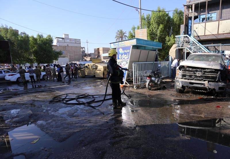 A firefighter hoses down a street after a suicide bomb attack in the city of Kerbala, Iraq, on June 9, 2017. Photo: Reuters