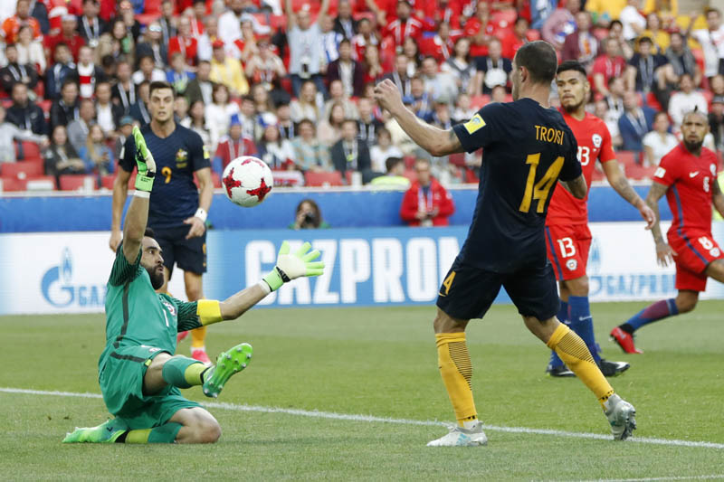 Australia's James Troisi, right, scores his side's first goal against Chile goalkeeper Claudio Bravo during the Confederations Cup, Group B soccer match between Chile and Australia, at the Spartak Stadium in Moscow, on Sunday, June 25, 2017. Photo: AP