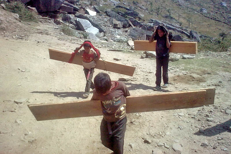 Children carry wood slices on their back to make money to pay their education bill in Kalikot district, on Thursday, June 1, 2017. Photo: RSS