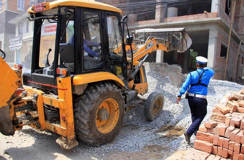 Traffic police clearing construction materials dumped on a road, in Lalitpur, on Wednesday, June 14, 2017. Photo: THT