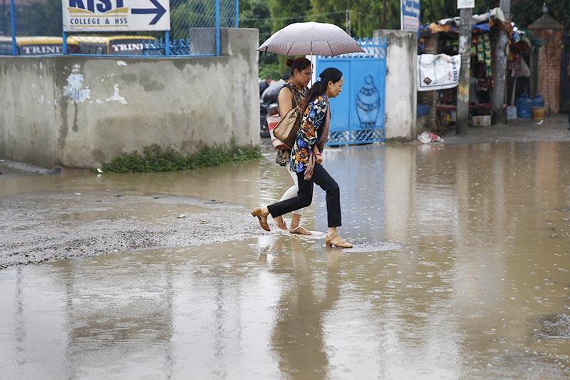 Women cross a water-logged road during a brief shower at Kamal Pokhari, Kathmandu, on Tuesday, June 20, 2017. photo: THT