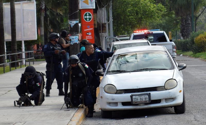 Policemen take cover behind a vehicle during a police operation to regain control of a prison, in Ciudad Victoria, in Tamaulipas state, Mexico, on June 6, 2017. Photo: Reuters
