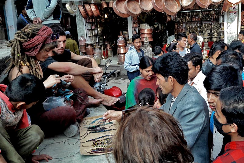 Foreign tourists are seen selling the handmade bracelets made by themselves, by the roadside in Asan, in Kathmandu district, Friday, June 30, 2017. Photo : RSS