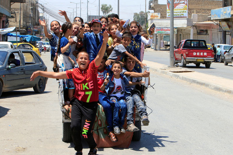 Iraqi children enjoy riding a mini car as they celebrate Eid al-Fitr, in Mosul, Iraq, on June 25, 2017. Photo: Reuters