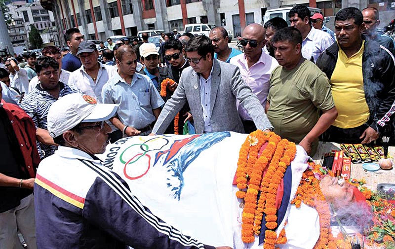 Olympian athlete Jeet Bahadur KC (left) and NOC President Jeevan Ram Shrestha (centre) draping Olympian lifter Sunil Lal Joshiu0092s body with NOC flag in Tripureshwor, Kathmandu, on Sunday. Photo: THT