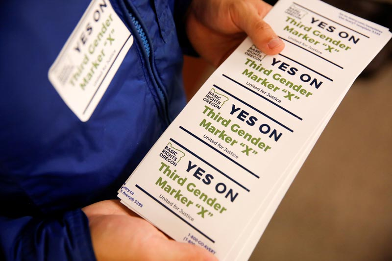 An employee of the advocacy group Basic Rights Oregon hands out stickers during an Oregon Driver and Motor Vehicle department public hearing on the rights of transgender people as the state considers adding a third gender choice to driver's licenses and identification cards, in Portland, Oregon, on May 10, 2017. Photo: Reuters