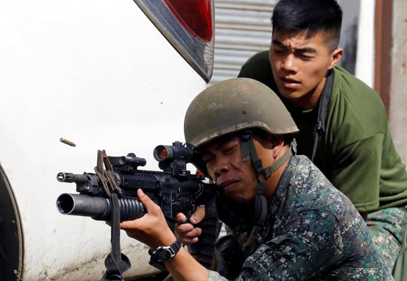 A Philippine Marine fires his weapon towards the stronghold of Maute group in Marawi City, southern Philippines. Photo: Reuters