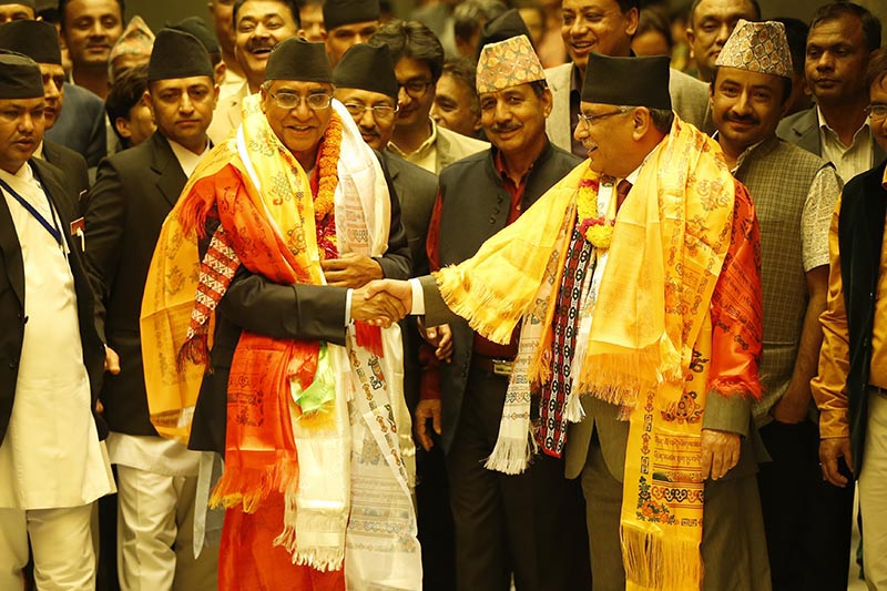 Newly elected Prime Minister Sher Bahadur Deuba shaking hands with the outgoing prime minister, Pushpa Kamal Dahal, after being elected to the top executive post, at the Legislature-Parliament, in Kathmandu, on Tuesday, June 6, 2017. Photo: Skanda Gautam/THT