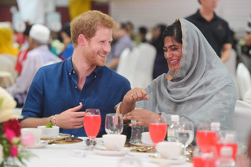 Britain's Prince Harry speaks to Nazhath Faheema, a Muslim Youth Ambassador of Peace, as they eat an evening meal to break fast, or the iftar, for Ramadan, during a visit to a children's home, on Sunday, June 4, 2017. Photo: Reuters