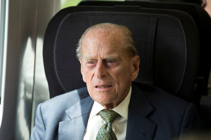 FILE- Britain's Prince Philip sits in a train on a journey marking the 175th anniversary of the first train journey by a British monarch, recreating the historic journey made by Queen Victoria on 13th June 1842, from Slough to London Paddington, Britain June 13, 2017. Photo: Reuters